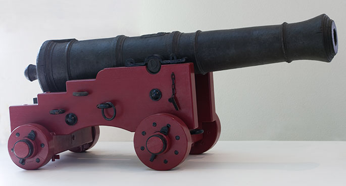 iron cannon on a red painted wooden base with four wheels