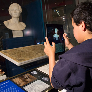 A boy viewing a museum object via an Ipad.