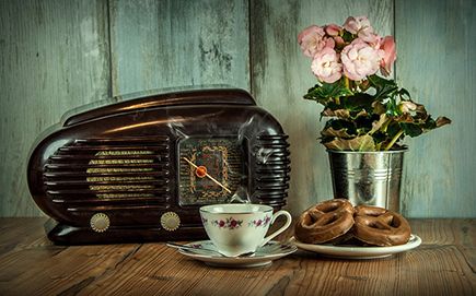 On old radio, a bucket of flowers, a cup and saucer, and a plate of biscuits.