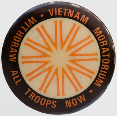 White, black and orange badge with the words Vietnam Moratorium/withdraw all troops now around the rim.