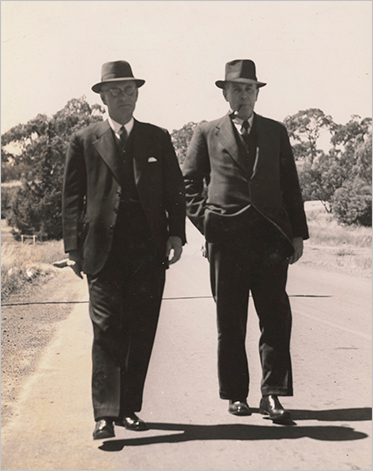 two men in suits and hats walk side by side outside.
