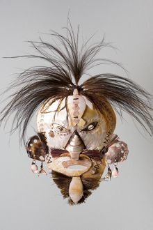 Cultural mask with white and brown tones and feathers for hair