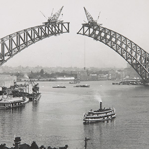 Photo taken from the north shore showing the two sides of the arch under construction. They have yet to meet. Large cranes are perched on top of each end of the spans. A ferry can be seen in the foreground.