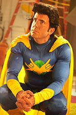 Man in a purple body suit, yellow cape and wig with an exaggerated hair style