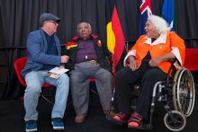 Two men and a woman in a wheel chair, on a stage