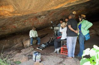 A man sits on a rock in a cave with rock art above, a video camera and five people at right
