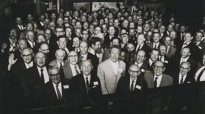 interior photo of tightly packed group of about 70 men in their 50s and 60s smiling at the camera.