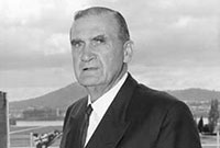 Man in a business suit with a mountain in the background