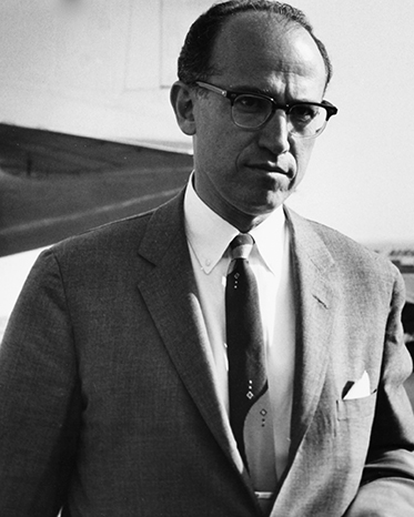 portrait of a serious-looking man of about 40 in a suit, with a receding hairline, wearing glasses