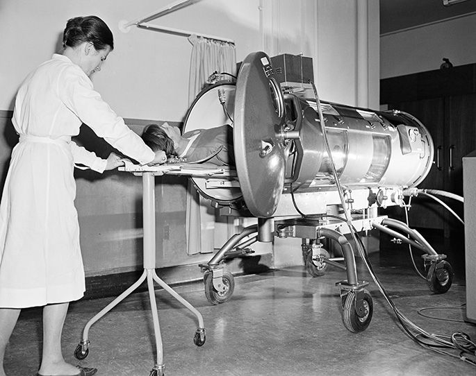 a black and white photo of a female nurse assisting a person inside a lung machine