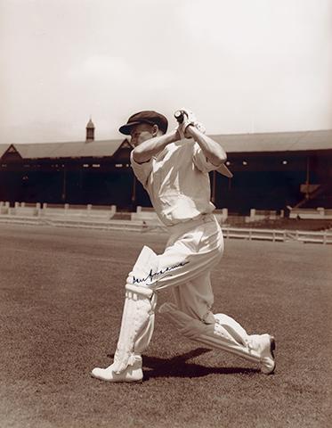 Batsman hitting ball, with stadium in background
