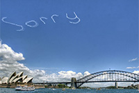 The word 'Sorry' written in white letters (by a plane). The sky is blue, Sydney Opera House and the Sydney Harbour Bridge form the backdrop