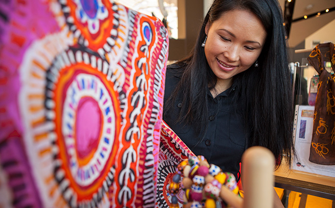 A woman looking at a scarf featuring Indigenous artwork.afts.