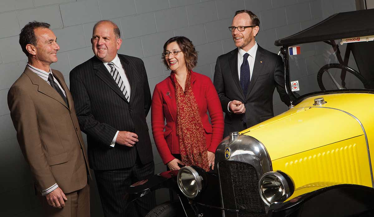The Executive of the National Museum of Australia standing beside a vintage car.
