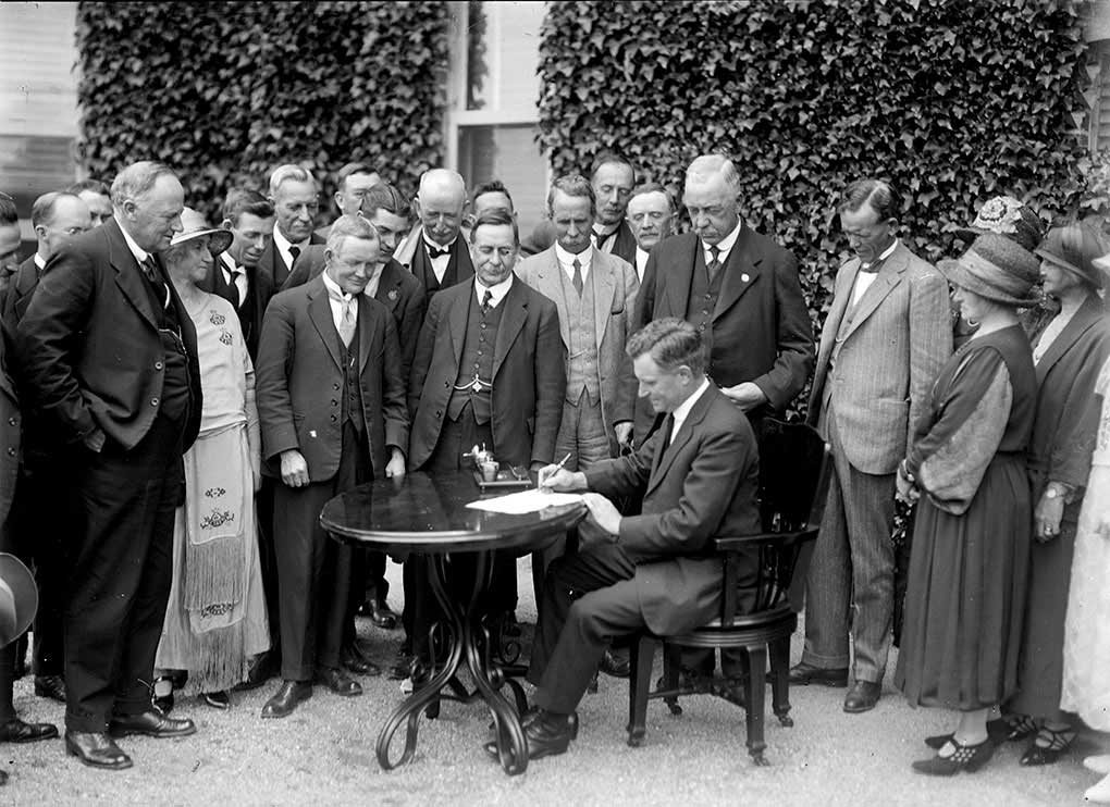 Black and white photo of a group of people watching a seated man at a table signing a document