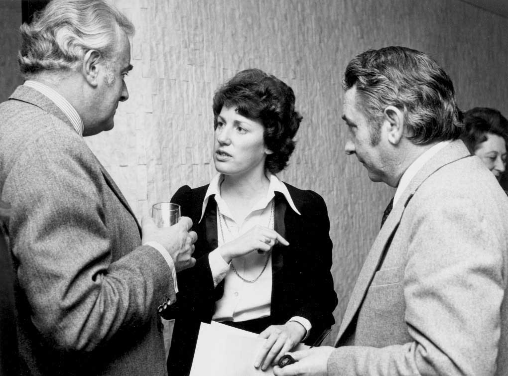 Interior photo. Woman in her thirties is speaking while Whitlam and Oswin listen.