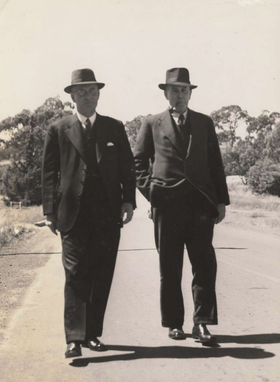 two men in suits and hats walk side by side outside. - click to view larger image