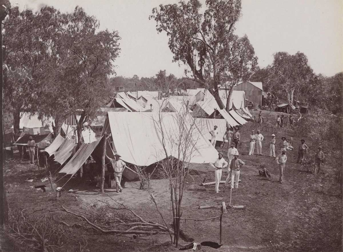 A black and white photo taken in the 1870s of a campsite.