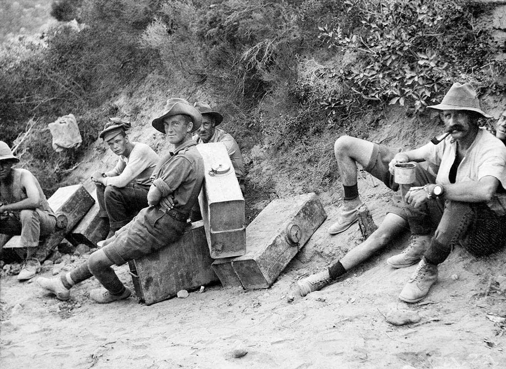 Black and white photo of a handful of Australian soldiers resting on or near their suitcase-sized water containers.