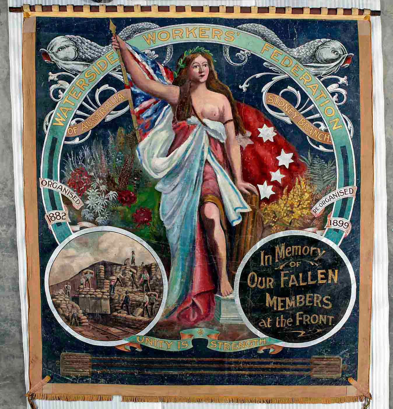 Large, almost square shaped banner painted in oil colours and showing a central image of a woman wearing loose flowing robes. She holds the red ensign and stands among native flowers. The text at the top reads 'Waterside Workers' Federation of Australia, Sydney branch'. An inset image at the bottom left shows workers handling numerous sacks and an inset at the bottom right reads 'In Memory of OUR FALLEN MEMBERS at the Front'. The motto 'Unity is Strength' joins the two insets. - click to view larger image