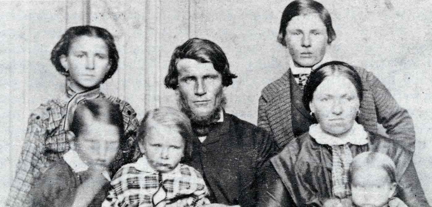 Black and white portrait showing a man and woman and five children.