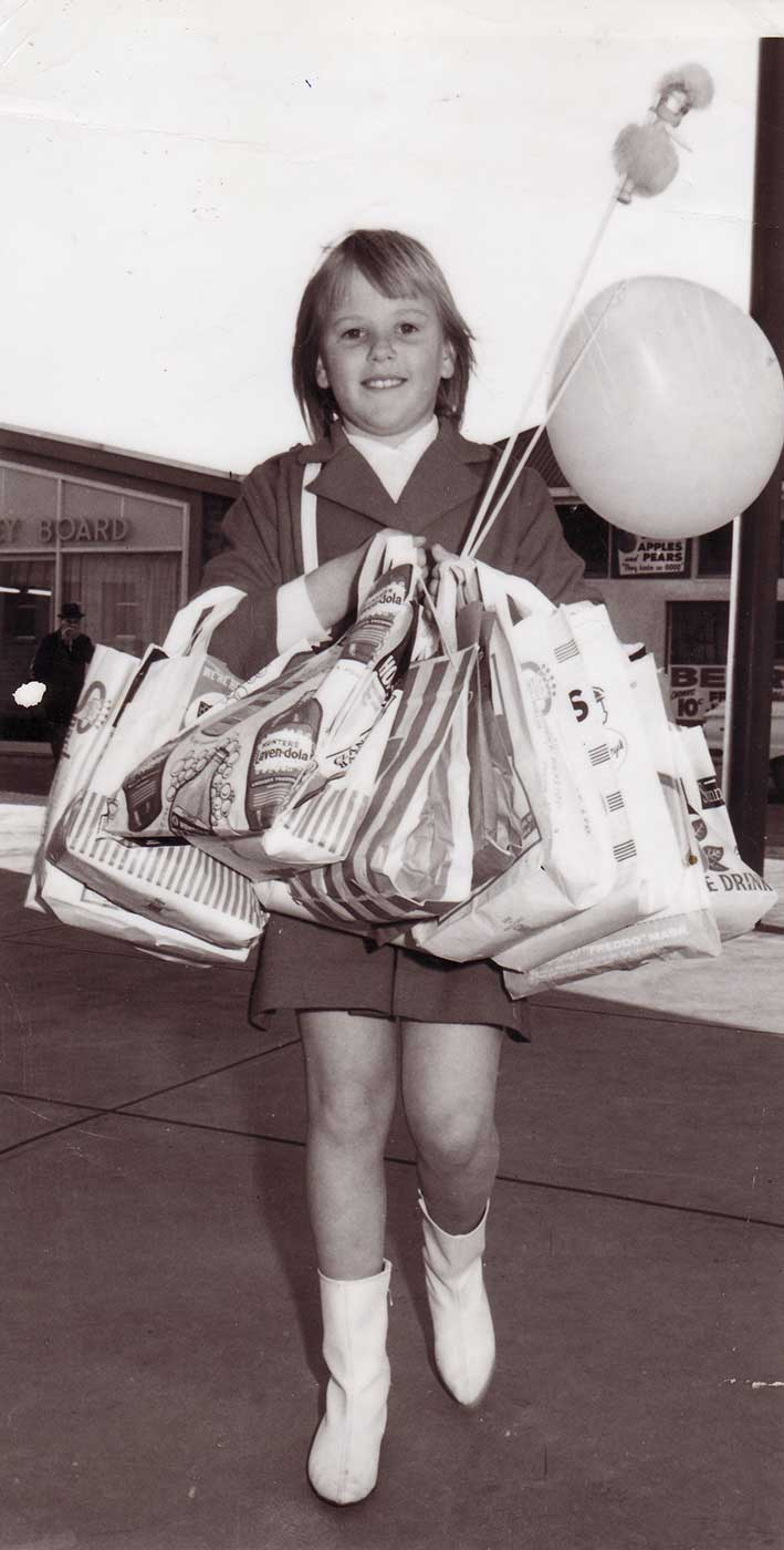 Black and white photograph of a young girl carrying multiple sample bags and a balloon and small doll on sticks. - click to view larger image