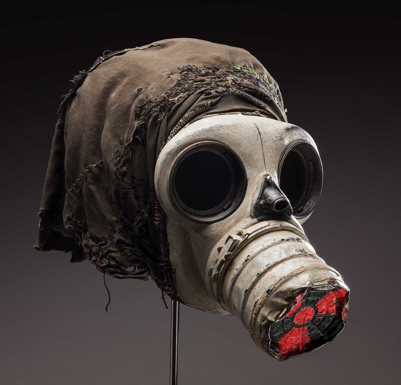 A gas mask with the end of the metal nose cone painted with a red and black nuclear symbol. Attached to the mask is a black fabric hood.  - click to view larger image