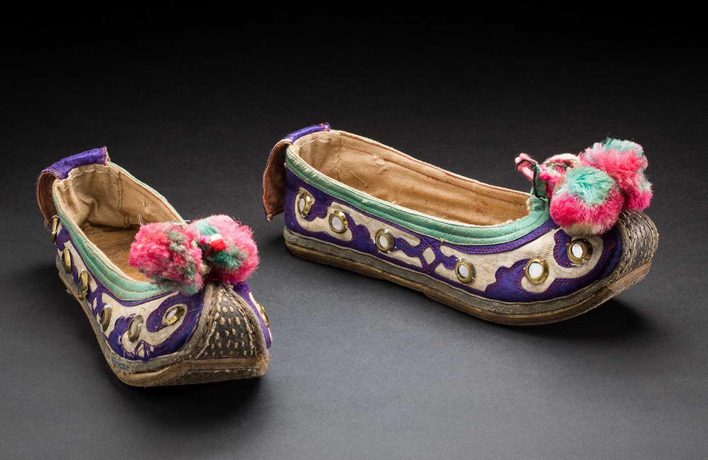 Colour photograph of two embroidered slipper-style shoes with upturned toes and pink and green pompoms at the end. - click to view larger image