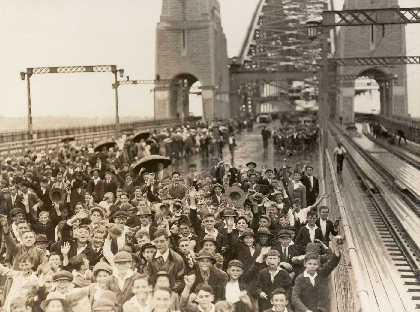 Black and white photo of a large crowd of schoolchildren crossing the Sydney Harbour Bridge. There is no traffic on the bridge. - click to view larger image