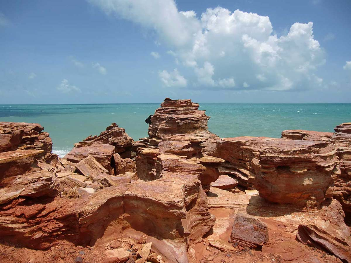 Colour photographs showing reddish rock formations overlooking the ocean. - click to view larger image