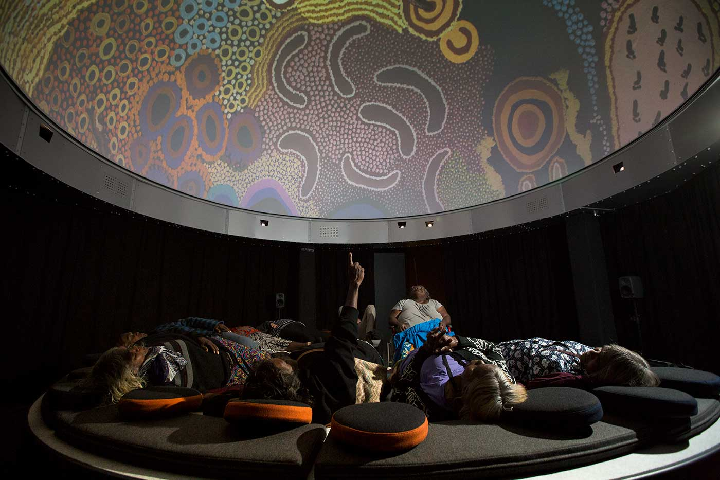 Group of women lying on padded surfaces and looking up at a dome with a digital screen - click to view larger image