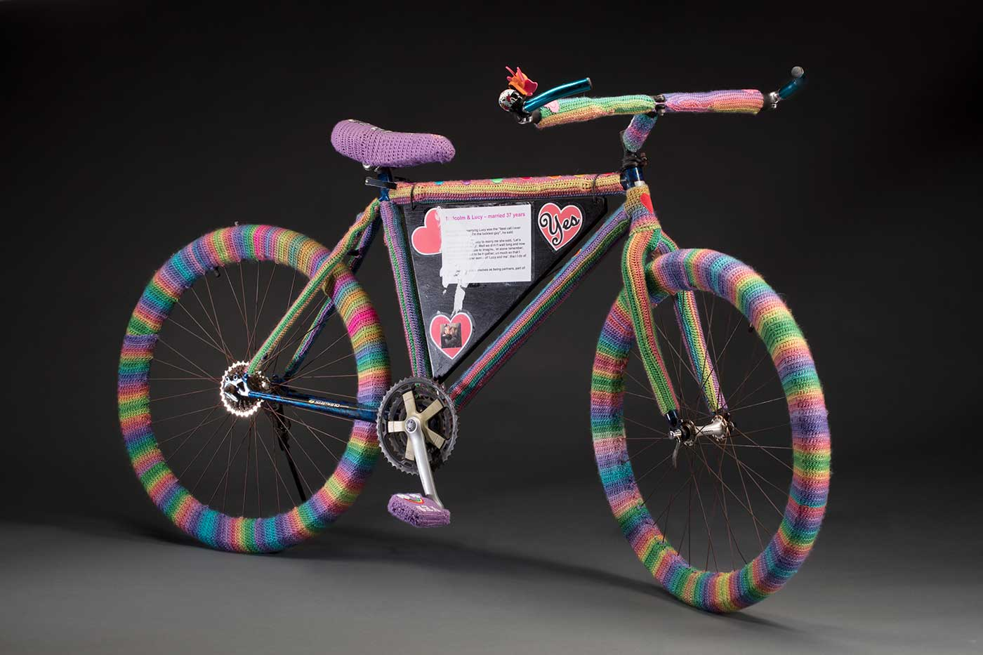 A bicycle covered with woollen crochet that consist of multi-coloured striped wheels, a purple seat and two purple peddles.
