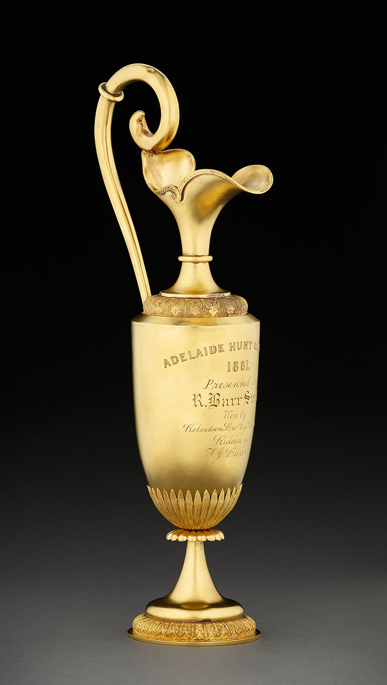 Side view of a gold trophy with scroll handle and ornate base. - click to view larger image