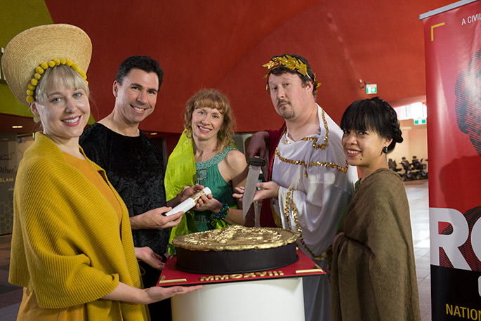 Five people dressed in costume surround a large cake in the form of a Roman coin
