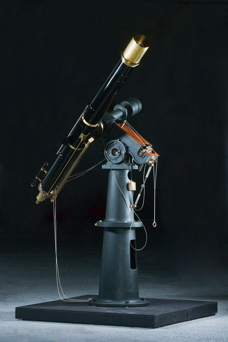 A black telescope made from cast iron and brass attached to a grey cast iron base. - click to view larger image