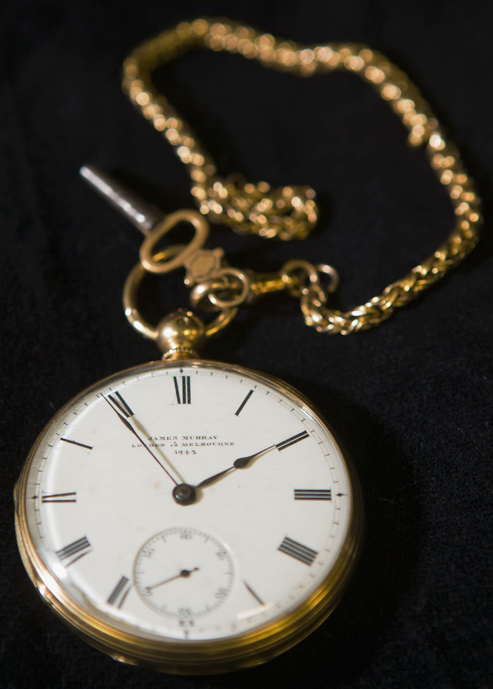 An open face pocket watch with an attached gold chain and key - click to view larger image