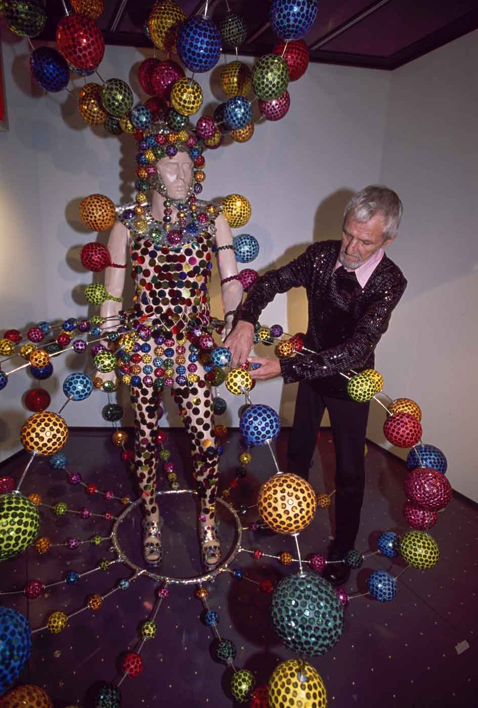 Man attaching sequinned ball to costume