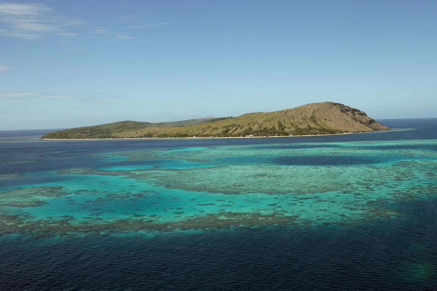 Photograph of an island surrounded by turquoise sea and reefs - click to view larger image