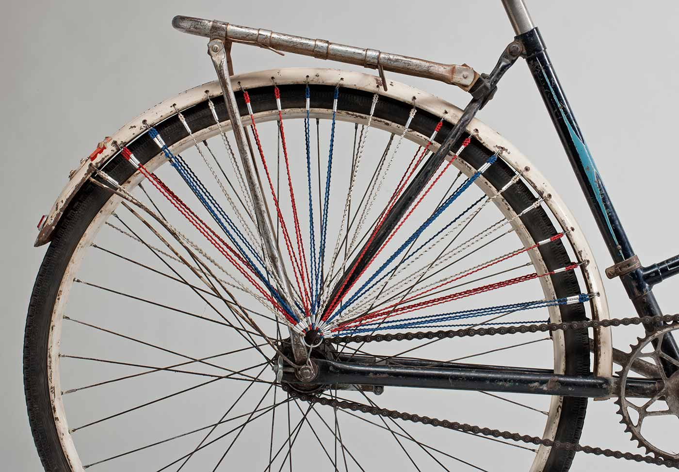 The rear wheel has lengths of red, white and blue fine cord attached through the mudguard and gathering just above the centre of the wheel; on both sides of the rear wheel.  - click to view larger image