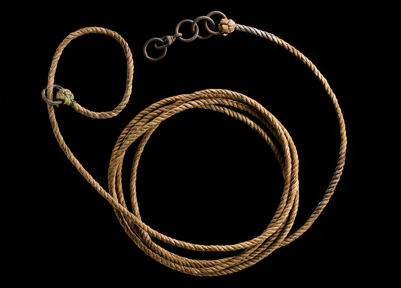 Bullock-hide rope with metal rings attached and arranged in a pleasing loop.