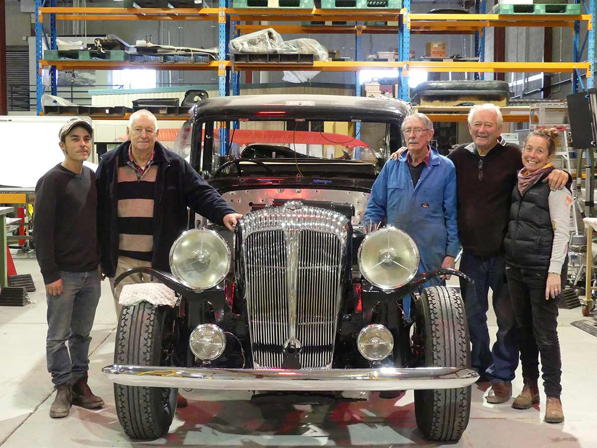 Five people standing either side of an old car with large headlamps and shiny, black paint. - click to view larger image