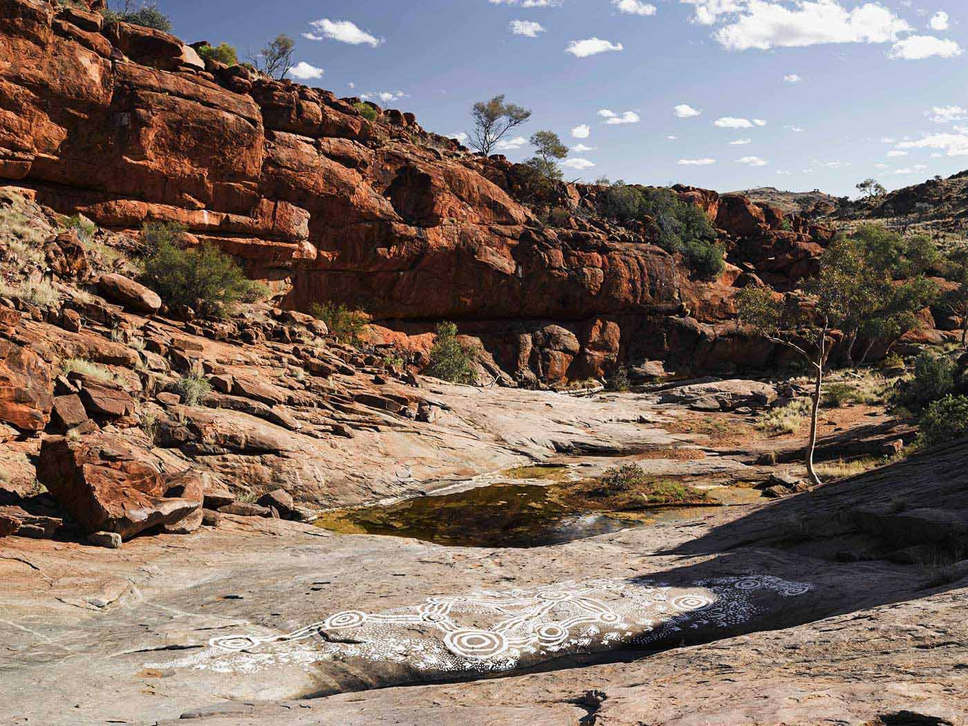 Colour photograph showing a rocky landscape. There is a small pool of water in the foreground with artwork in white designs painted on a smooth and flat rock surface nearby. - click to view larger image