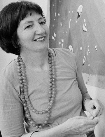 A black and white portrait photo of a woman. Part of an embroidery artwork is hanging on the wall behind her.