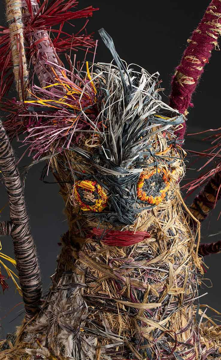A detail image of a tree sculpture's human like face. It is made of various plant and synthetic materials. - click to view larger image
