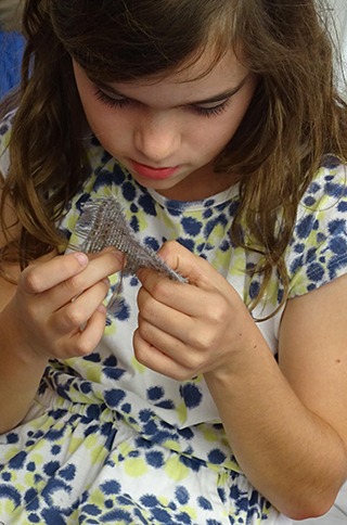 A child is studying a small square piece of loosely woven fabric which she is holding with both hands.