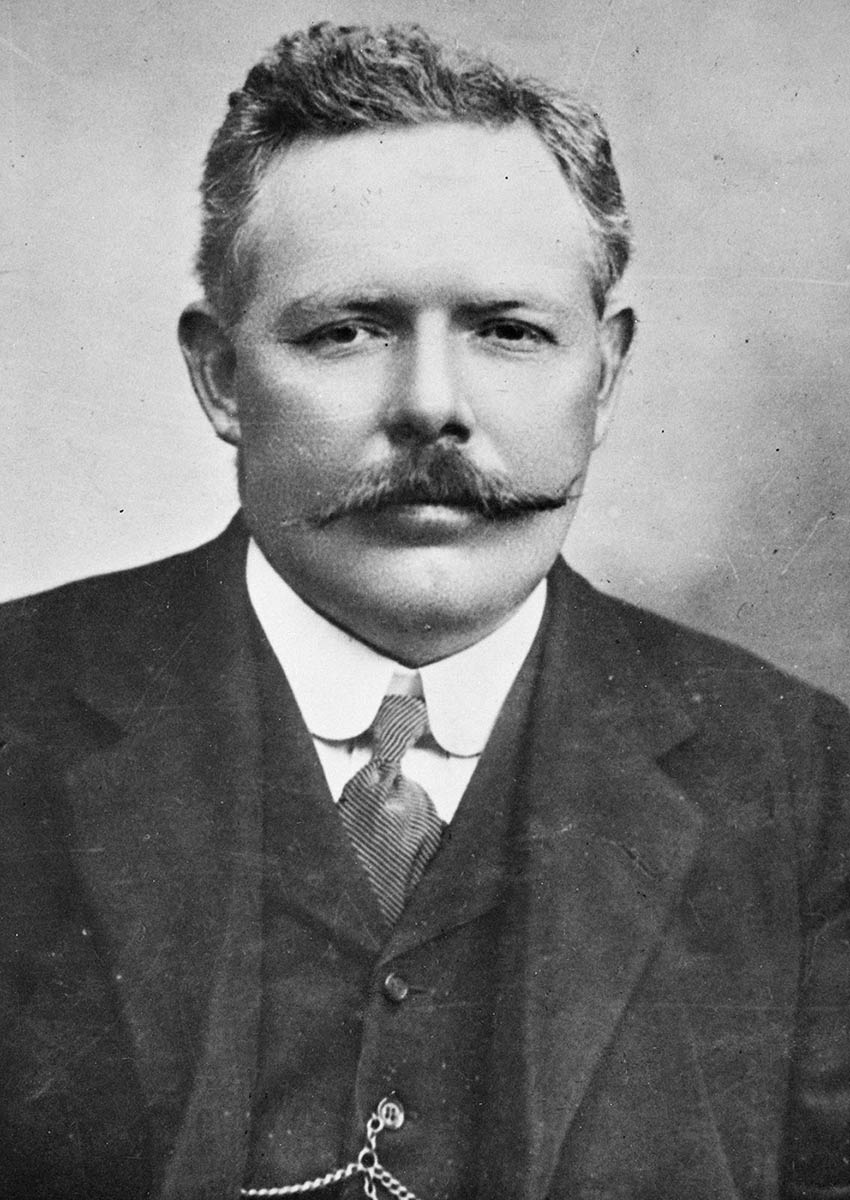 Photo of a man sporting a moustache and wearing a suit.