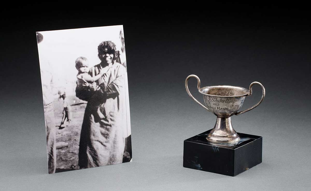 Black and white photograph of a woman holding a baby; and a small mounted silver cup.