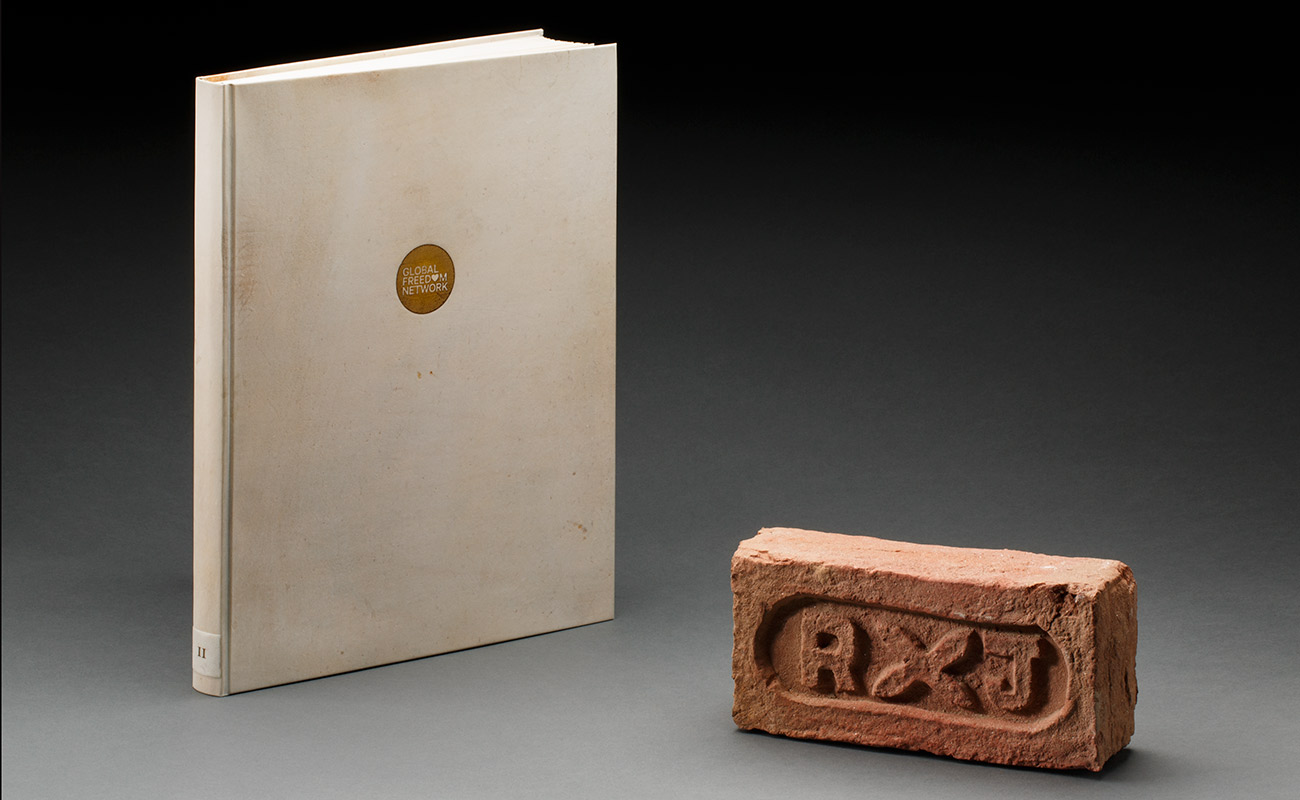 A cream coloured hard-covered book and a red-brown clay brick.