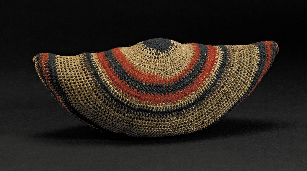 A semicircular shaped woven bag of wool and twine, with patterns of red and blue.