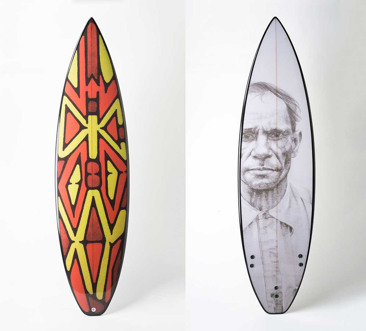 A fibreglass surfboard featuring a rainforest shield design on the front, with a portrait in black and white on the reverse.